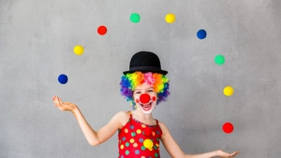 Little girl dressed as a clown juggling coloured balls